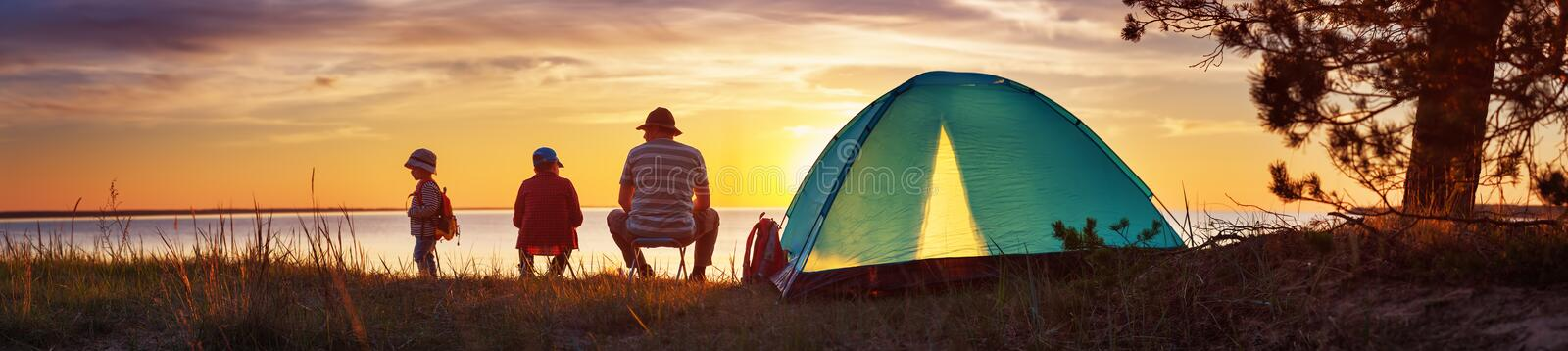 Family resting with tent in nature at sunset royalty free stock images