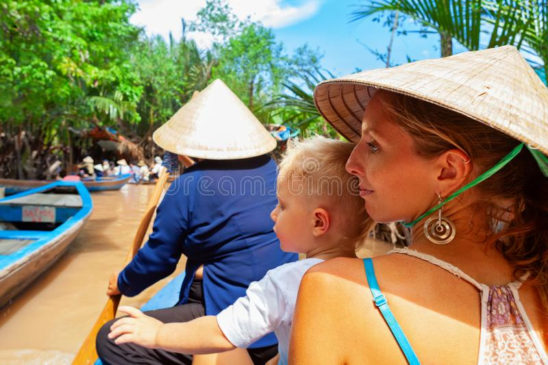 Family ride on traditional Vietnamese boat in Mekong river delta stock photo