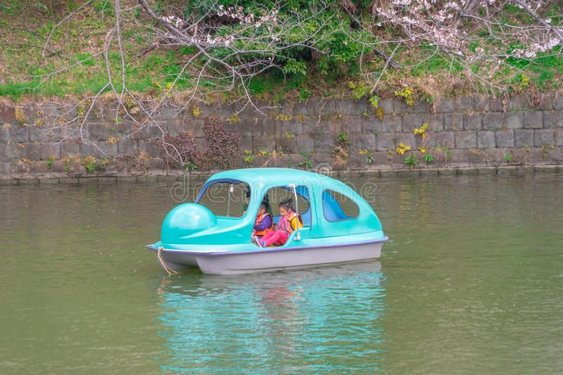 Family riding on paddle boat in Tokyo Chidorigafuchi Sakura park royalty free stock photo