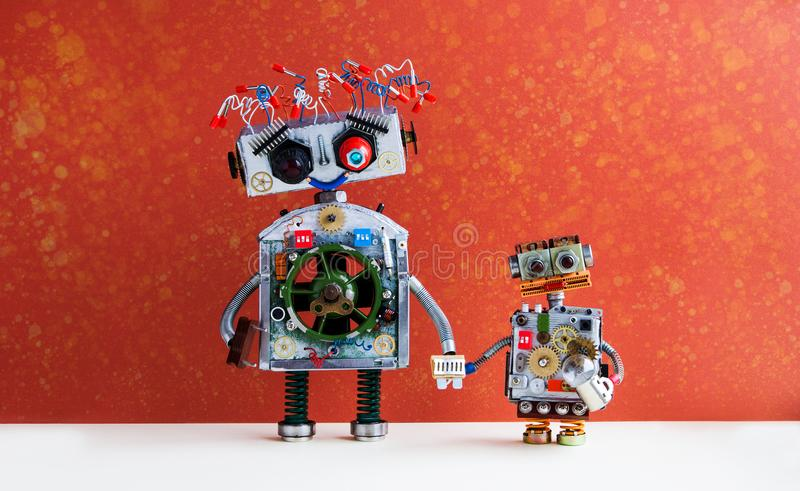 Family robots. Big robot mom holds the hand of a small child robot. Creative design futuristic cyborg toys on red wall. Background royalty free stock photos