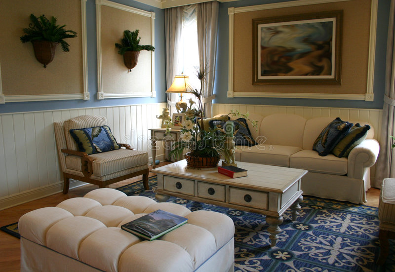 Family room. Blue and white family room with carpet, wall hangings, coffee table, chair and sofa