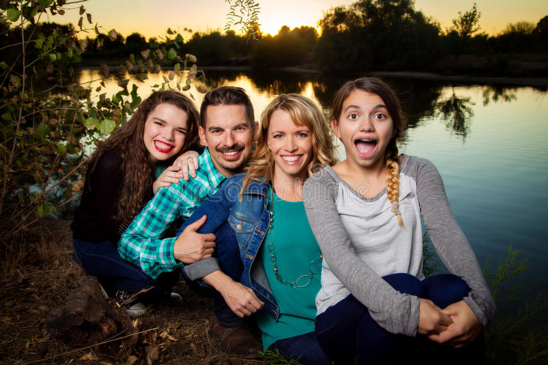 Family Row. A good looking family sits in a row. Mother, father, and two teenage girls. The daughter in front has a surprised look on her face royalty free stock photos