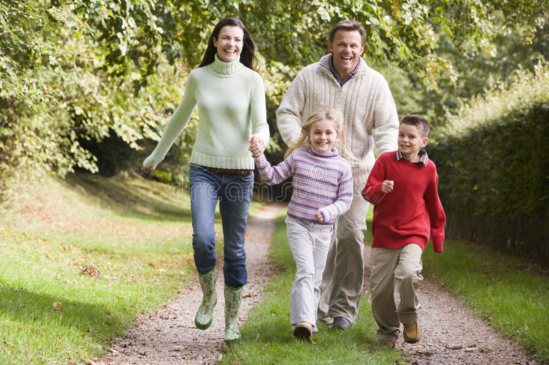 Family running along woodland track. In autumn