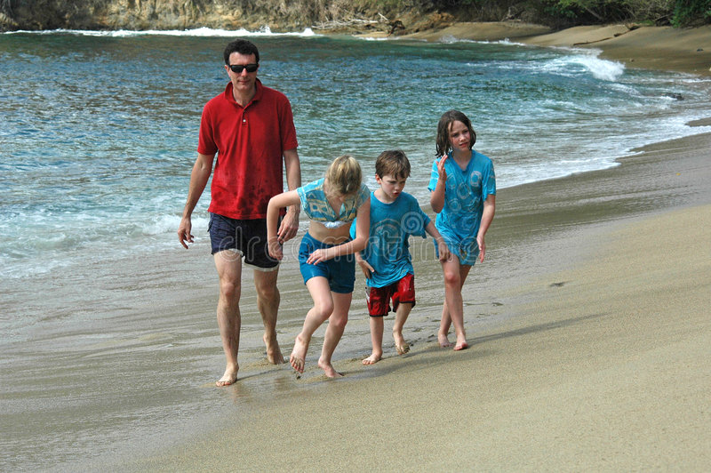 Family running on the beach. Father and three children running on beach, Nikon D70 royalty free stock photos