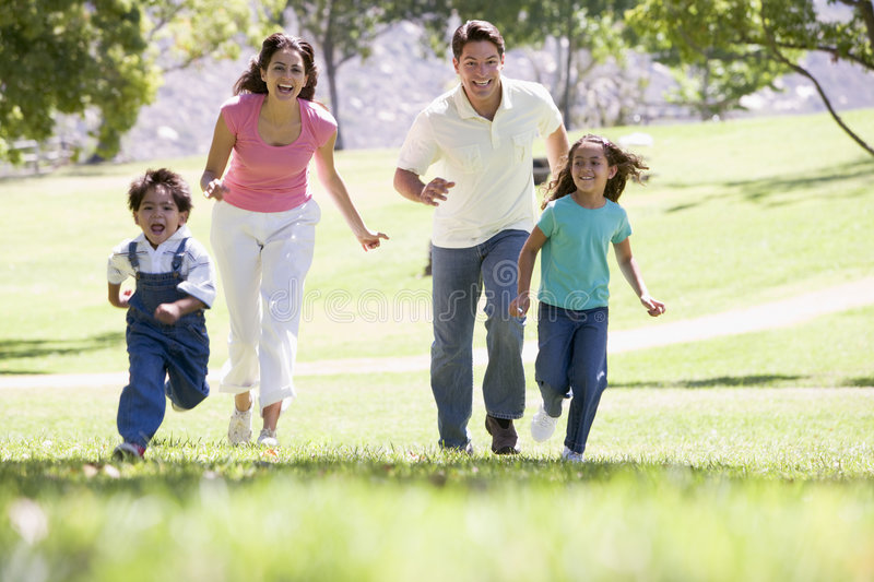 Family running outdoors smiling stock photo