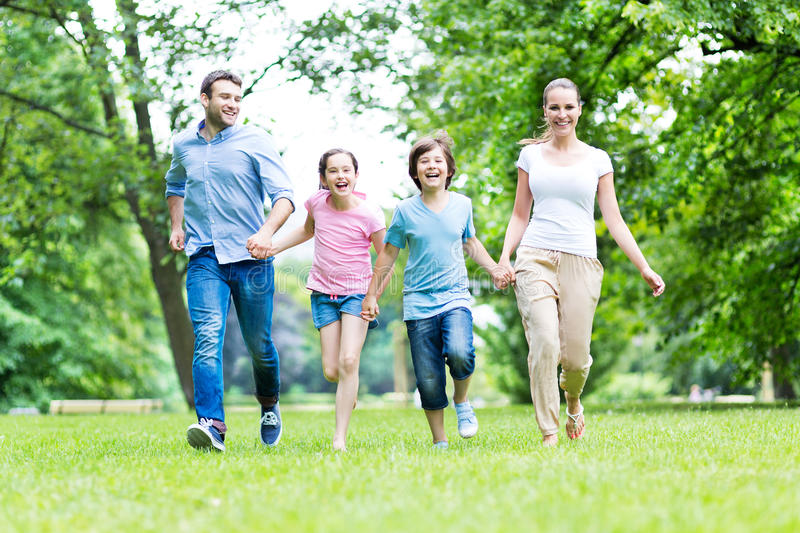 Family running in the park stock photography