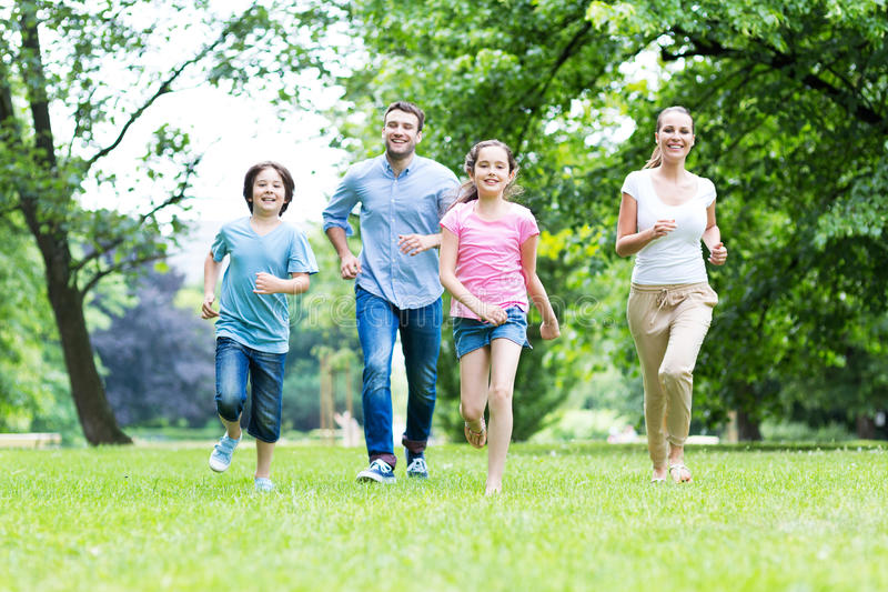 Family running in the park stock image