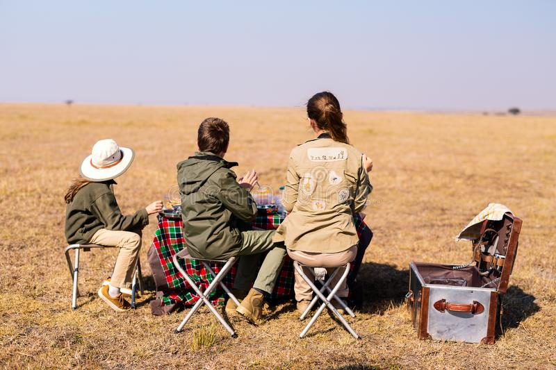 Family safari breakfast. Back view family of mother and kids on African safari vacation enjoying bush breakfast stock images