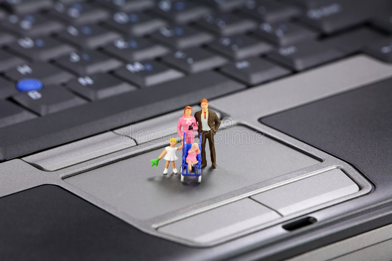 Family safe internet. A miniature family stands on a laptop. Family safe internet surfing concept stock photos