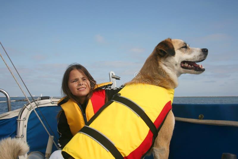 Family sail. Akita and Australian shepard mixed breed dog and girl sailing across the water stock photos