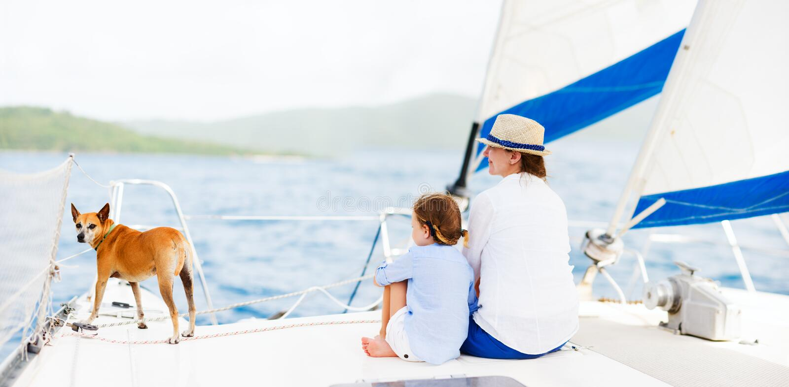 Family sailing on a luxury yacht. Back view of mother, daughter and their pet dog sailing on a luxury yacht or catamaran boat royalty free stock photography