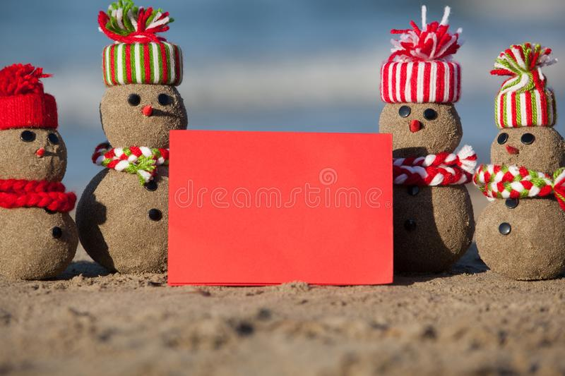 Family of sandy Snowmen at tropical beach with blank card. royalty free stock photos
