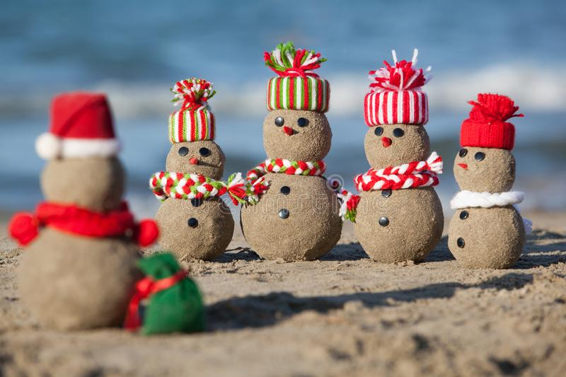 Family of sandy Snowmen at tropical beach. stock images