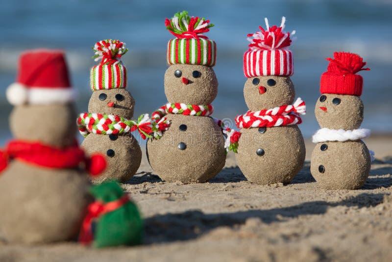 Family of sandy Snowmen at tropical beach. stock photos