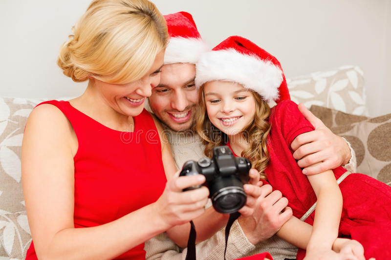 Family In Santa Helper Hats Looking At Pictires Stock Image