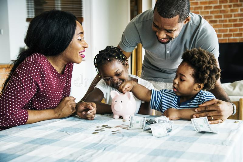 Family saving money in piggy bank royalty free stock photos