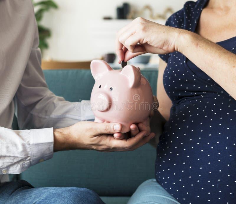 Family saving money in piggy bank stock image