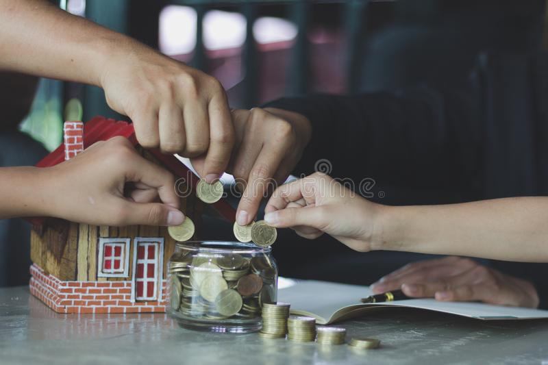 Family saving money putting coins into glass bank, Savings plans for housing, financial concept royalty free stock images