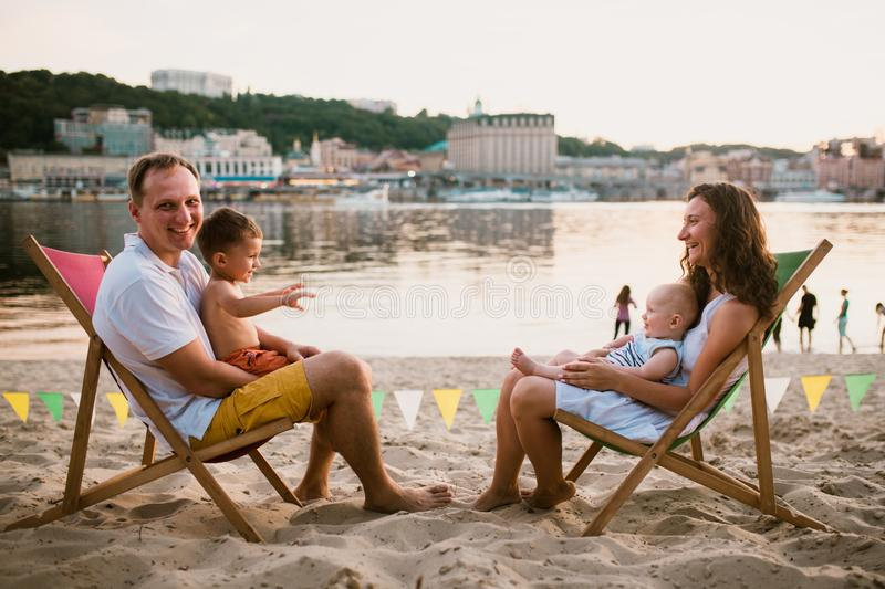 Family at seaside in evening open-air cafe. Mother and father and two sons sit on sun loungers, looking at sunset on sandy beach stock photo