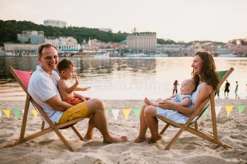Family at seaside in evening open-air cafe. Mother and father and two sons sit on sun loungers, looking at sunset on sandy beach stock image