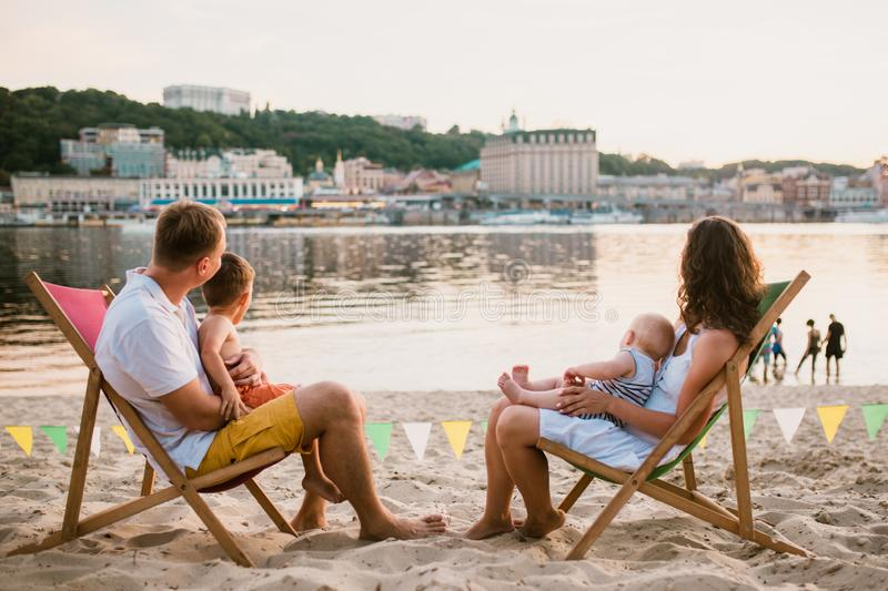 Family at seaside in evening open-air cafe. Mother and father and two sons sit on sun loungers, looking at sunset on sandy beach. Near river overlooking city stock photo