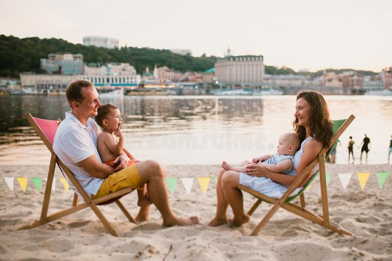 Family at seaside in evening open-air cafe. Mother and father and two sons sit on sun loungers, looking at sunset on sandy beach royalty free stock photos