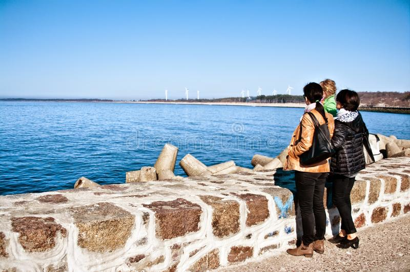 Family on seawall at Baltic Sea royalty free stock photography