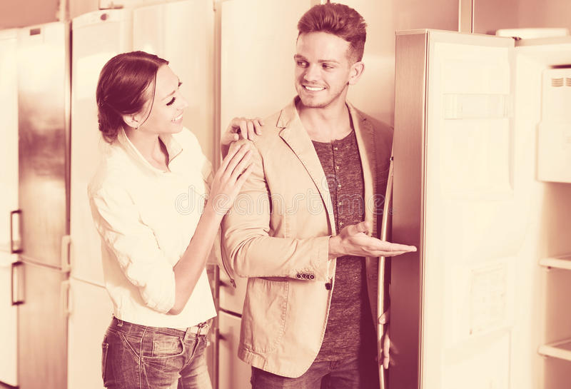 Family selecting fridges in domestic appliances store stock image