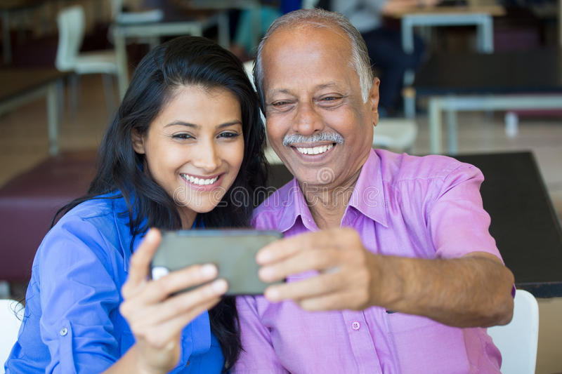 Family selfie. Closeup portrait happy elderly gentleman in pink shirt and lady in blue top taking selfie together, isolated indoors background. Say cheese and stock photos