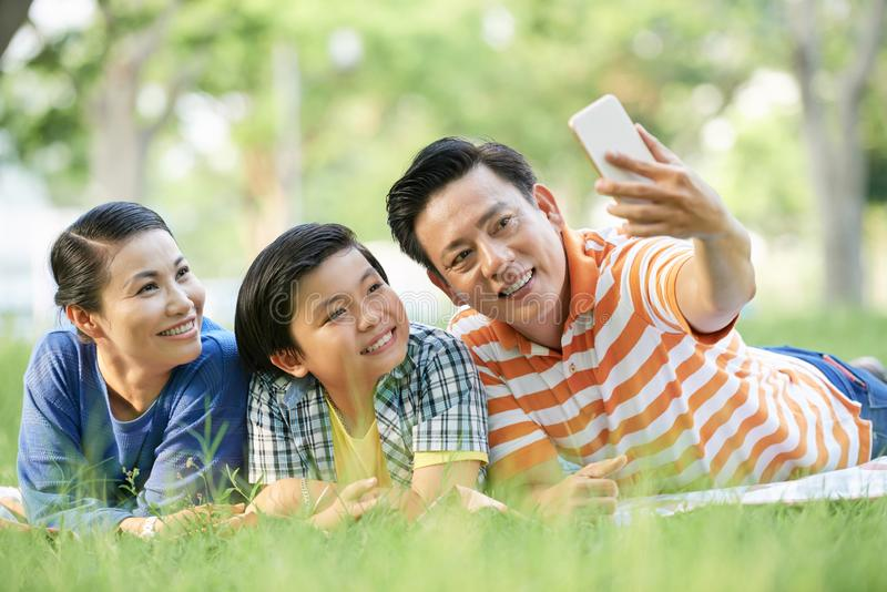 Family selfie. Middle-aged Vietnamese man taking selfie with with wife and teenage son royalty free stock image