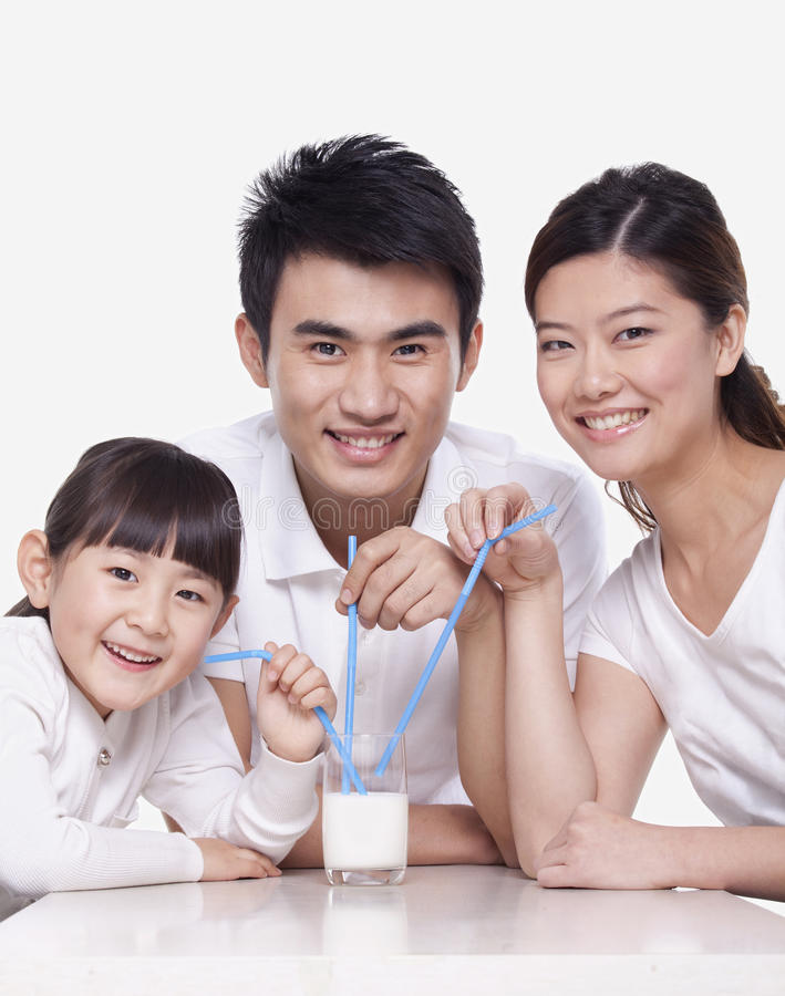 Family sharing a glass of milk, studio shot royalty free stock photography