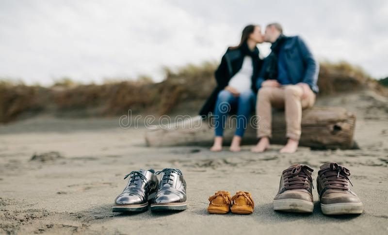 Family shoes in the sand with couple kissing royalty free stock photography