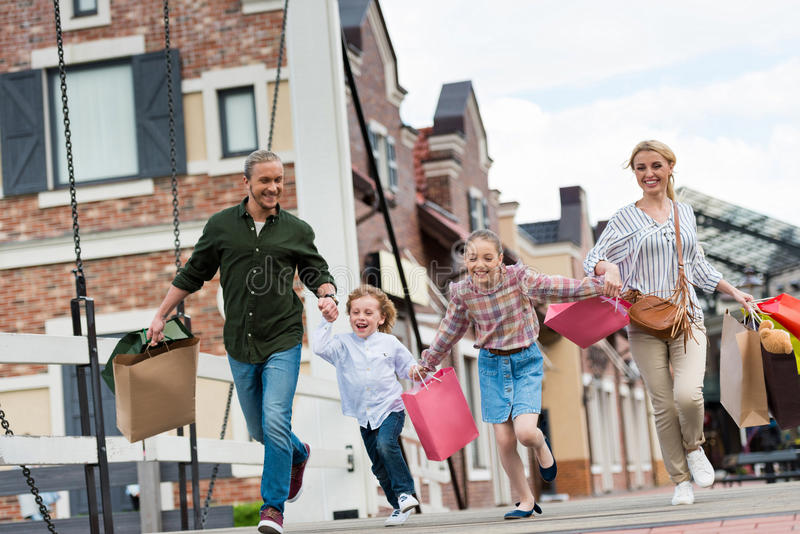 Family with shopping bags holding hands and walking while shopping stock images