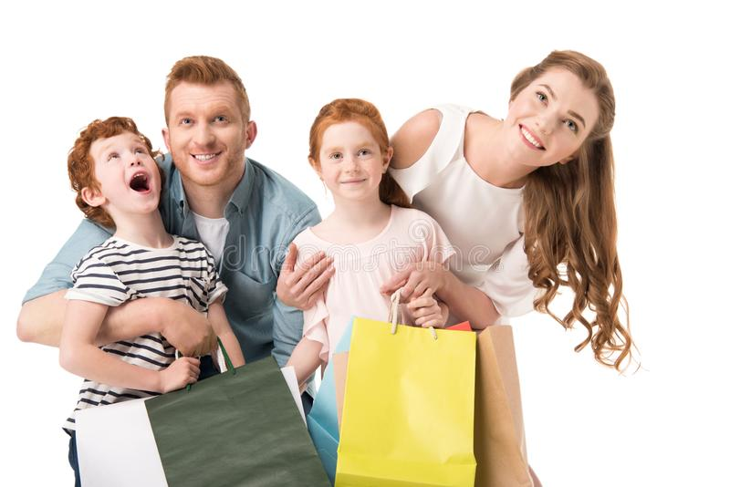 Happy young family with two kids holding shopping bags. Isolated on white royalty free stock photos