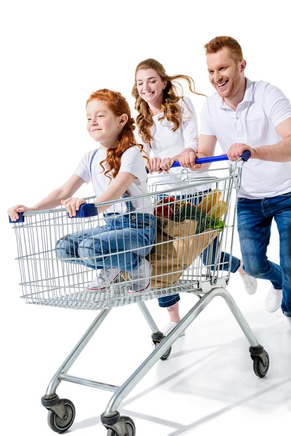 Happy young parents carrying cute redhead daughter in shopping cart. Isolated on white stock photo
