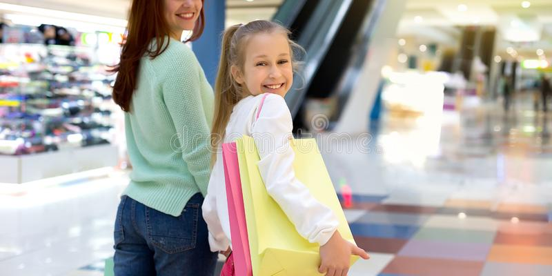Family shopping. Little child holding shopping bags in city mall royalty free stock image
