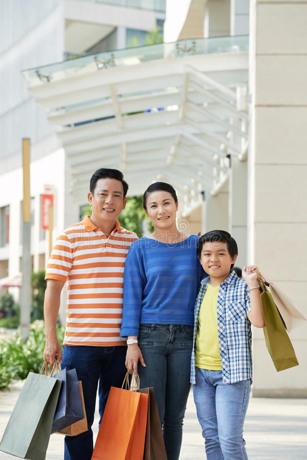 Family in shopping mall. Positive Vietnamese family with paper-bags shopping in mall royalty free stock photos