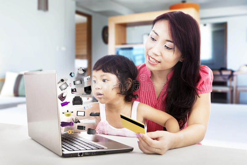Family shopping online. Happy mother and daughter shopping online with laptop at home stock images