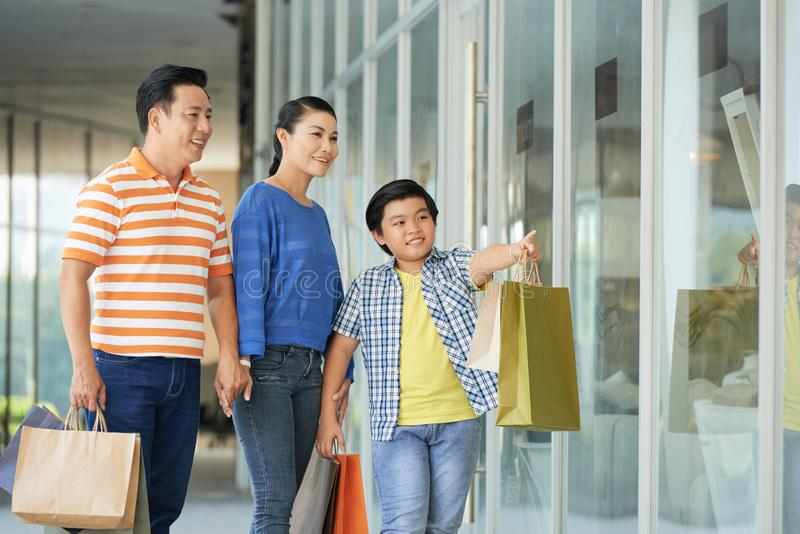 Family shopping together. Vietnamse teenage boy showing his parents something interesting in shop window stock photography