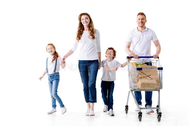Happy young family with two kids walking with shopping trolley. Isolated on white royalty free stock images