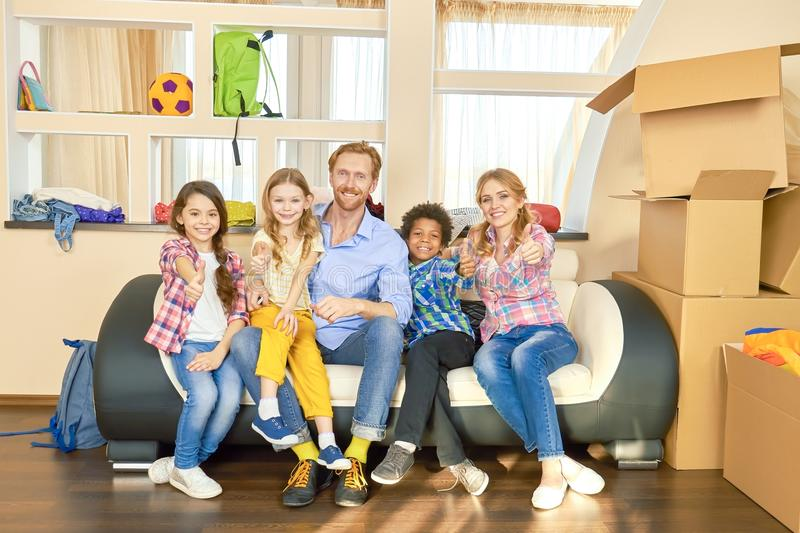 Family showing thumbs up, boxes. stock photo