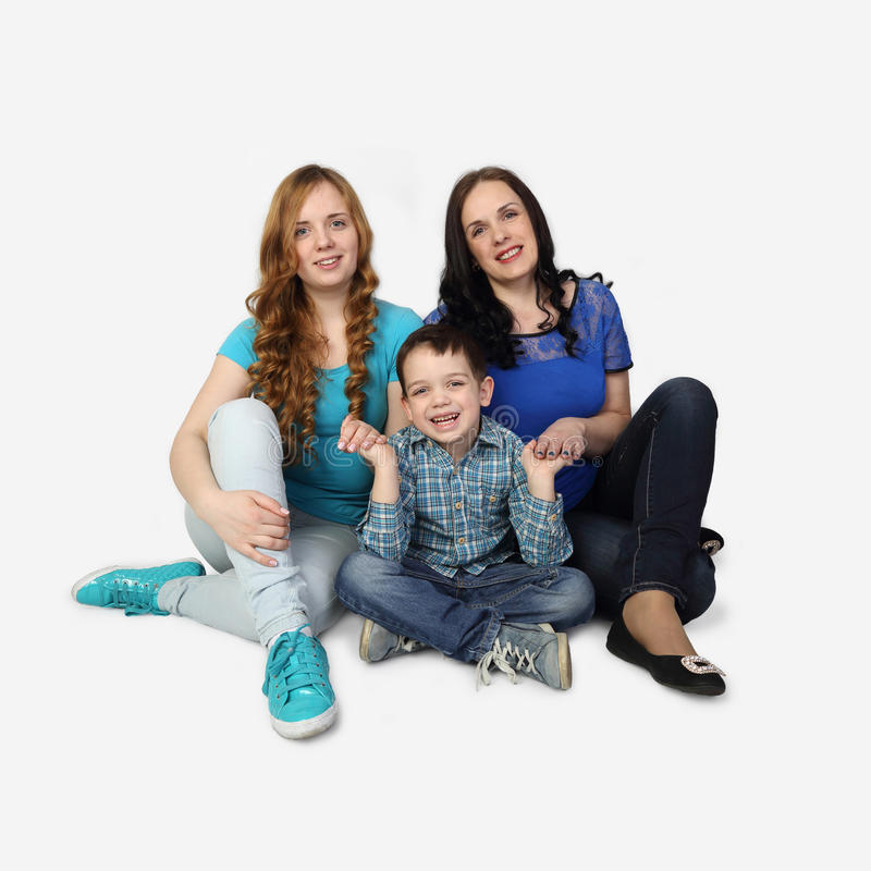 Family sit on floor on gray. Woman, girl and little boy sit on floor on gray background - Incomplete family portrait stock image