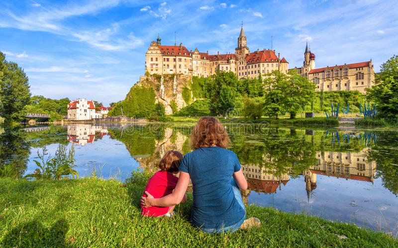 Family sit near medieval Sigmaringen Castle, Germany. Young woman and her child are at river shore in summer royalty free stock image