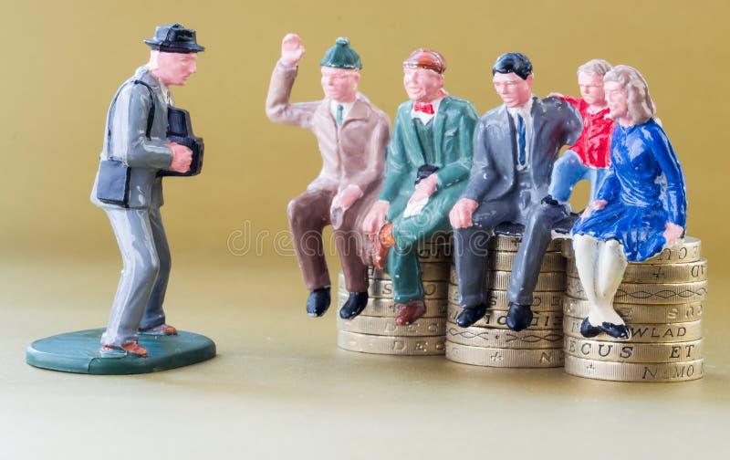 Family Sits modelo em moedas de libra britânica fotografia de stock royalty free