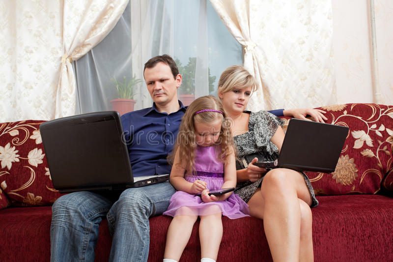 Family sits on a sofa royalty free stock photo