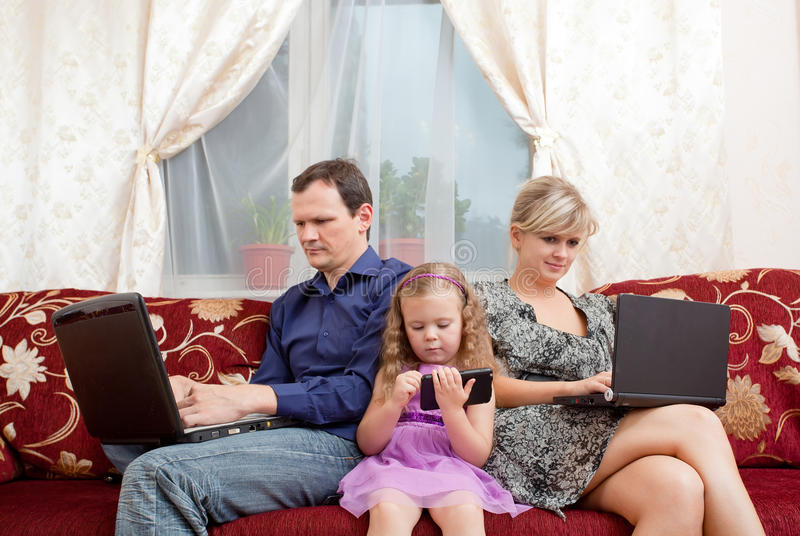 Family sits on a sofa stock image
