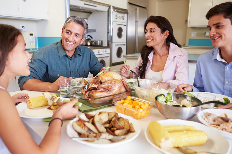 Family Sitting Around Table At Home Eating Meal. Chatting To Each Other stock photo