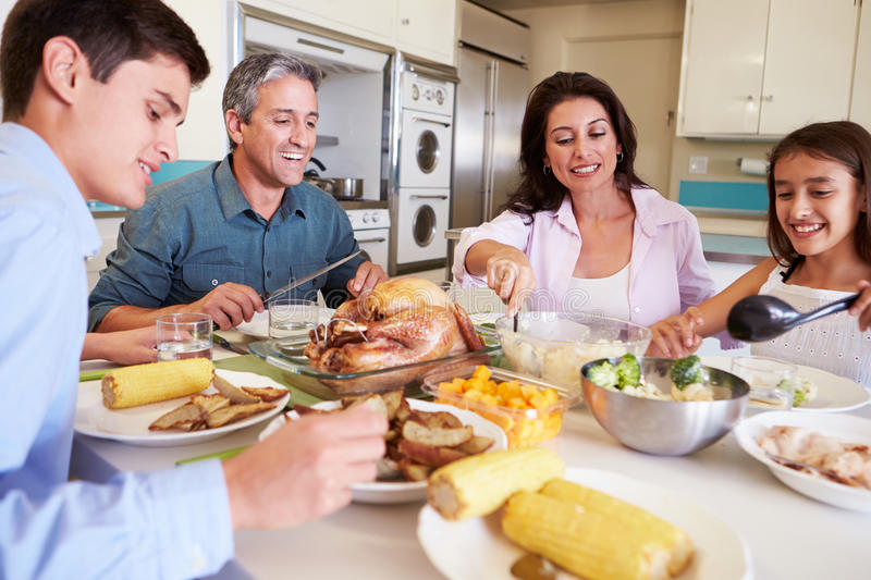 Family Sitting Around Table At Home Eating Meal. In Kitchen Smiling stock photography