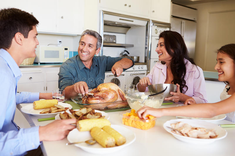 Family Sitting Around Table At Home Eating Meal. Looking At Each Other Smiling stock photography