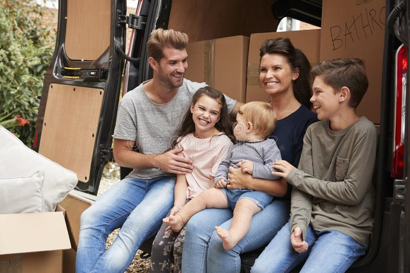 Family Sitting In Back Of Removal Truck On Moving Day stock photos